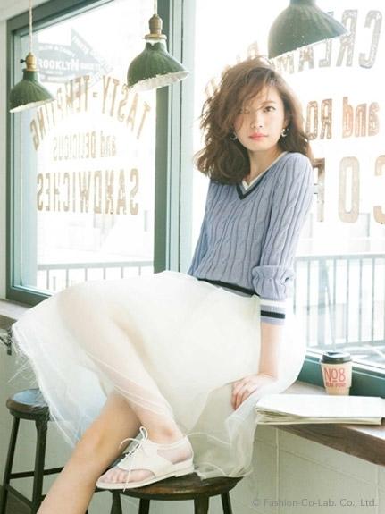 セーターに白いスカートを合わせたファッションの宮田聡子