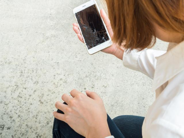 画面が割れたスマートフォンを持つ女性